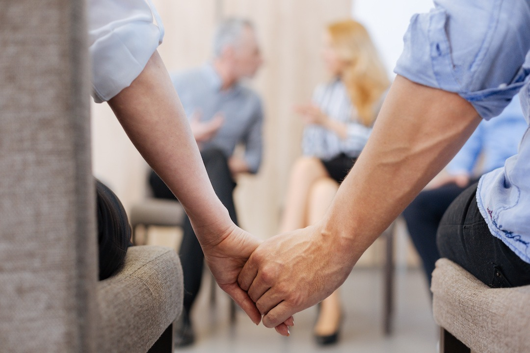 Couple sitting together and holding their hands while showing their unity in marriage counseling and marriage retreat