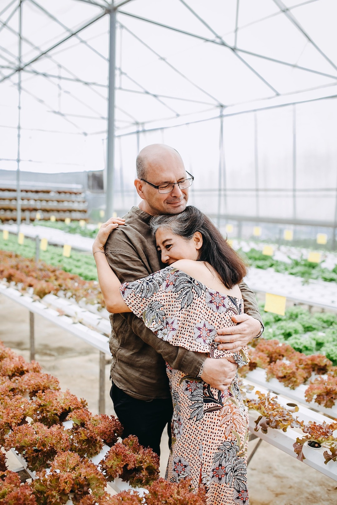 Couple hugging while in a green house after going through couple's therapy