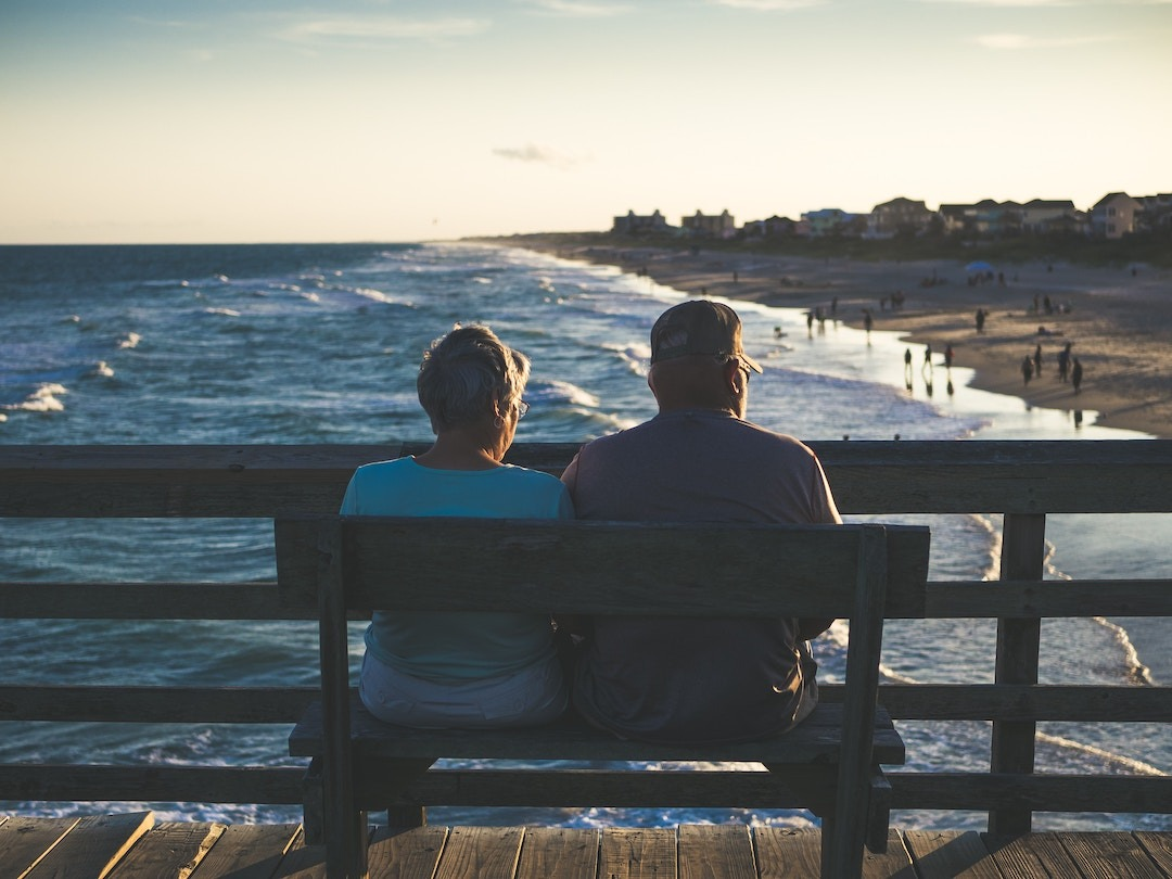 Older couple enjoying the view of the ocean while going on a couple's retreat and receiving couple's therapy